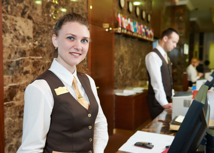 27855345 - happy female receptionist worker standing at hotel counter