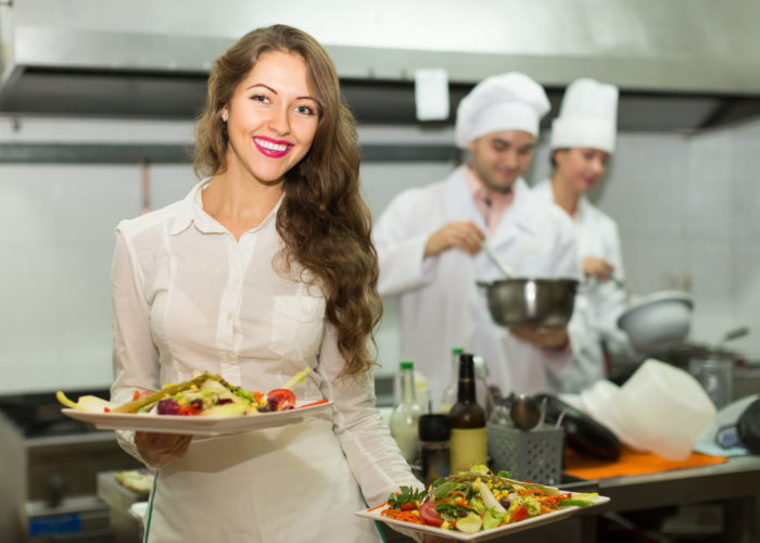 36298951 - beautiful smiling female waiter taking dish from kitchen in cafe