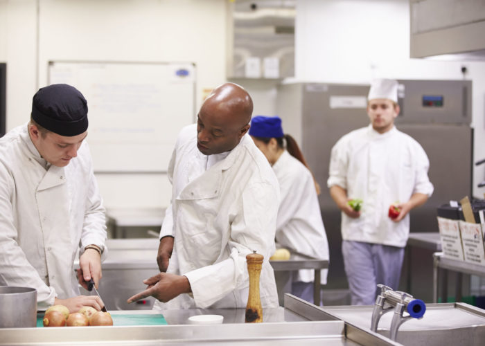 42311673 - teacher helping students training to work in catering